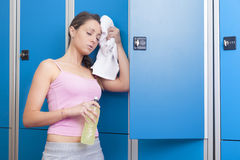 Fitness young smiling woman resting in blue dressing room Royalty Free Stock Photo