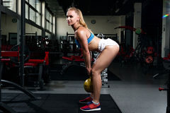 Fitness young sweaty girl with a sports body in a gym doing exercises with a weight royalty free stock photos