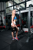 Fitness young sweaty girl with sports body in the gym holds weight for the bar stock photography