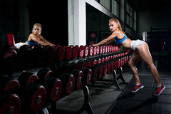 Fitness young sweaty girl with a sports body in the gym is sexually standing near a number of dumbbells is preparing to do stock photography