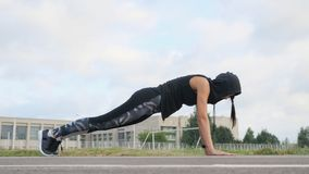 Fitness young woman athlete doing plank exercise on stadium royalty free stock photography