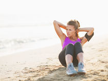 Fitness young woman doing abdominal crunch on beach Stock Image