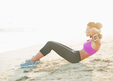 Fitness young woman doing abdominal crunch on beach. Fitness young woman in sportswear  doing abdominal crunch on beach Stock Photography