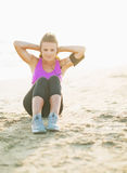 Fitness young woman doing abdominal crunch on beach Stock Images