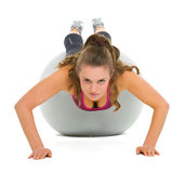 Fitness young woman doing push ups on fitness ball Royalty Free Stock Photos