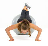 Fitness young woman doing push ups on fitness ball Stock Photo