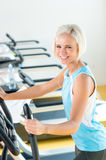 Fitness young woman on elliptical cross trainer Royalty Free Stock Image
