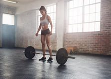 Fitness young woman at gym with barbell. Full length portrait of fitness young woman standing at gym with barbells on floor. Muscular young female athlete at stock photos