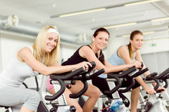 Fitness young woman on gym bike spinning. Indoor cardio exercise Stock Image