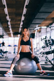 Fitness young woman in gym resting on Pilates ball Stock Image