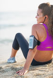 Fitness young woman in headphones sitting on beach Stock Image