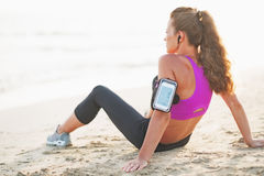 Fitness young woman in headphones sitting on beach Stock Photography