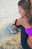 Fitness young woman in headphones sitting on beach Stock Photos
