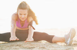 Fitness young woman in headphones stretching on beach Stock Photography