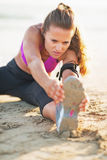 Fitness young woman in headphones stretching on beach Royalty Free Stock Photography