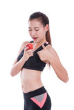 Fitness young woman holding apple and showing thumb up Royalty Free Stock Images
