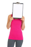 Fitness young woman holding blank clipboard in front of face Royalty Free Stock Images