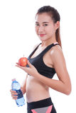 Fitness young woman holding a bottle of water and an apple. Over white background Royalty Free Stock Photo