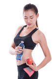 Fitness young woman holding a bottle of water and an apple. Over white background Royalty Free Stock Images