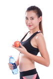 Fitness young woman holding a bottle of water and an apple. Over white background Royalty Free Stock Photos