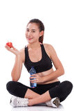 Fitness young woman holding a bottle of water and an apple. Sitting on the floor over white background Stock Photo