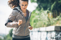Fitness young woman jogging in the city park royalty free stock image