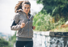 Fitness young woman jogging in the city park Royalty Free Stock Images