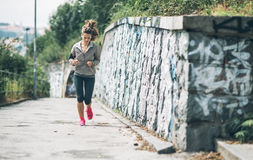 Fitness young woman jogging in the city park Stock Photos