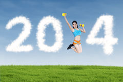 Fitness young woman jumping with new year 2014. Happy fitness young woman jumping with new year 2014 of clouds Royalty Free Stock Image