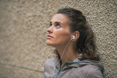 Fitness young woman listening music outdoors Royalty Free Stock Image