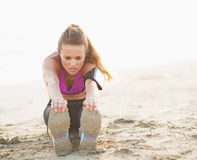 Fitness young woman making exercise on beach Royalty Free Stock Photo