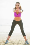 Fitness young woman making exercise on beach Stock Photo