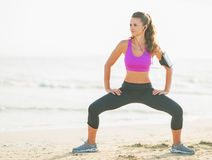 Fitness young woman making exercise on beach Stock Image