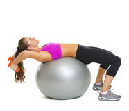 Fitness young woman making exercise with dumbbells on fitness ball Royalty Free Stock Image