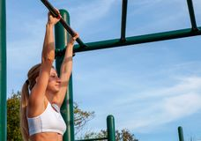 Fitness young woman pulls up on the horizontal bar. royalty free stock images