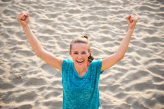 Fitness young woman rejoicing on beach Stock Images