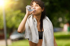 Fitness young woman resting and drinking water after training Stock Photos
