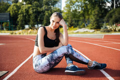 Fitness young woman resting on running track Stock Photos
