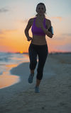 Fitness young woman running on beach at dusk Royalty Free Stock Photos