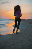 Fitness young woman running on beach at dusk . rear view Royalty Free Stock Image