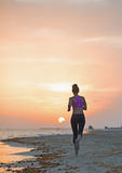 Fitness young woman running on beach in the evening Stock Images