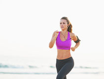 Fitness young woman running on beach. Fitness young woman with long hair running on beach Stock Images