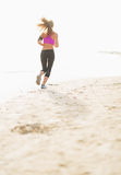 Fitness young woman running on the beach . rear view Stock Images