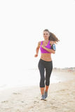 Fitness young woman running on the beach Stock Photography