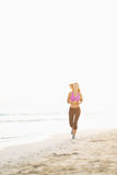 Fitness young woman running on beach Stock Photo