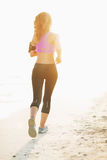 Fitness young woman running on beach Stock Photos