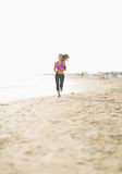 Fitness young woman running on beach Royalty Free Stock Images