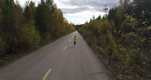 Woman running on forest trail. Fitness young woman running on forest trail stock video footage