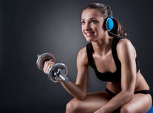 Fitness young woman sitting on the ball lift weights and listeni Royalty Free Stock Photography
