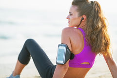 Fitness young woman sitting on beach. rear view Stock Photo